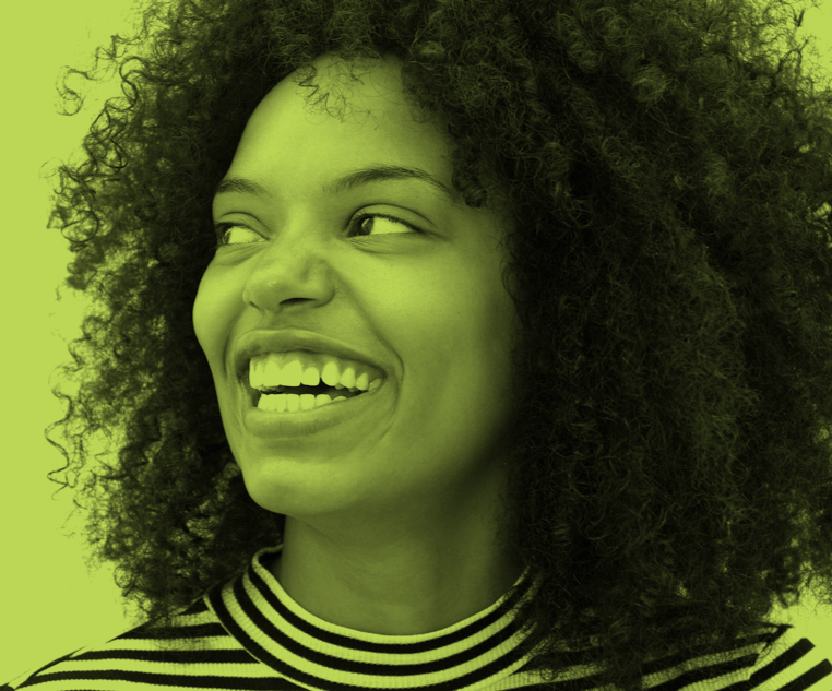 Woman with curly hair smiling widely and looking to the right.